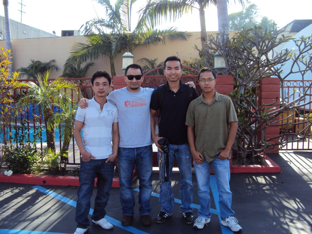 Four men standing for a photo outside.