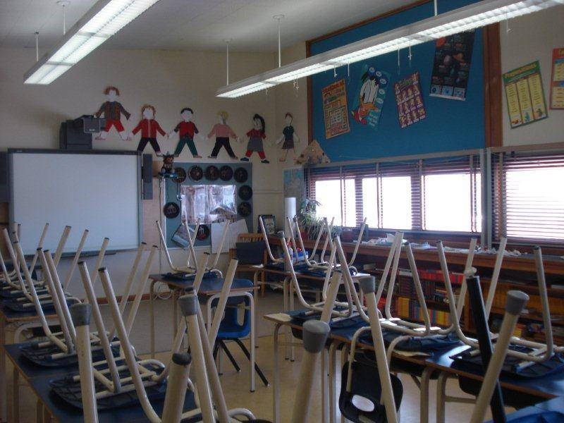 Photo of a classroom with chairs on the desks.