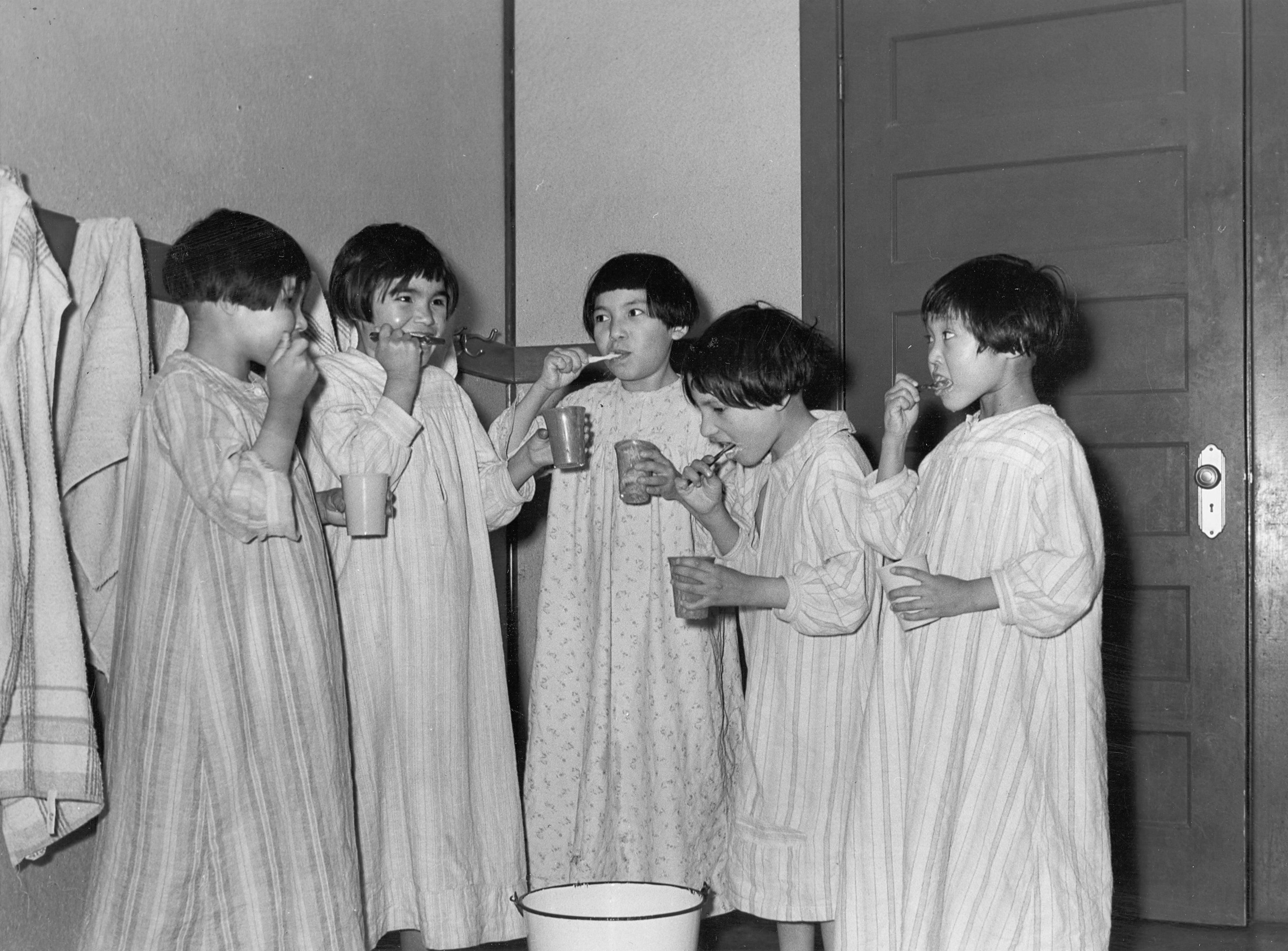 Black and white photo of girls brushing their teeth.